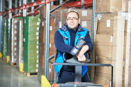 registros contables: Male worker with barcode scanner in modern warehouse