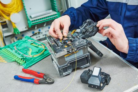 Ingénieur technicien travaillant avec la fusion à l'arc machine épissage lors de la connexion par câble à fibre optique Banque d'images - 64443045