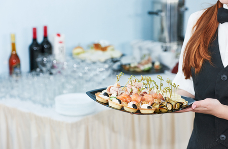 servicio de catering camarera. personal femenino plato de servicio completo de comida rápida en el evento de restaurante