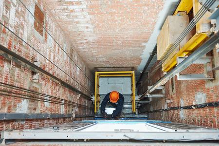 Los técnicos de los trabajadores en el trabajo de maquinista de ajuste mecanismo de elevación en forma de elevación del ascensor Foto de archivo - 64969045