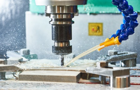 Milling metalworking process. Industrial CNC machining of metal detail by cutting end-tooth vertical mill at factory Stock Photo