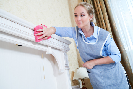 hotel staff: Cleaning service. Female hotel staff worker clean bed from dust Stock Photo