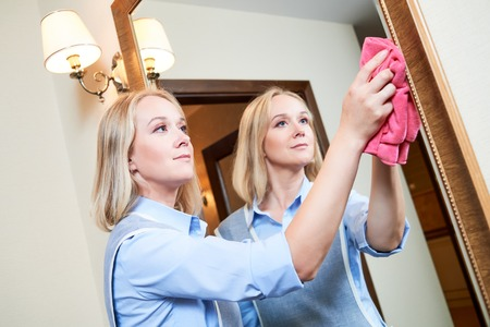 hotel staff: Cleaning service. Female hotel staff worker clean wall mirror from dust and spot