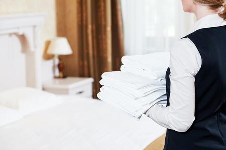 Hotelservice. Housekeeping Zofe mit Handtüchern und Bettwäsche Bettwäsche im Zimmer Standard-Bild - 62299354