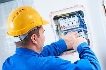fuse box: electrician with screwdriver repair or fixing high voltage switching electric actuator in fuse box