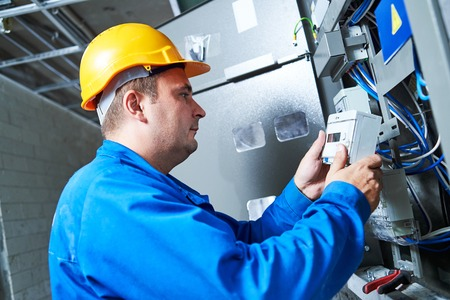 service man: Electrician installing energy saving meter into switch box panel