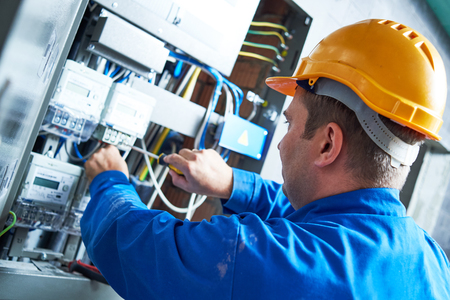Electrician installing energy saving meter into switch box panel