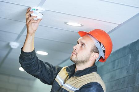 trabajador de la construcción la instalación de alarma del detector de humo en el techo