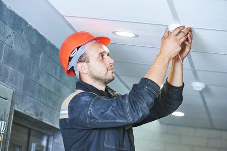Handyman werknemer het installeren of het controleren rookmelder detector aan het plafond Stockfoto - 62299645