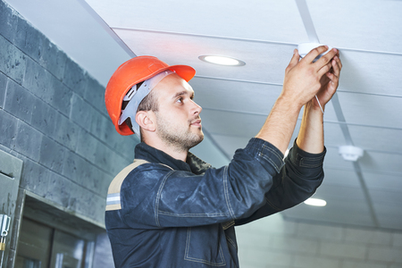 Handyman worker installing or checking smoke alarm detector on the ceiling Banque d'images