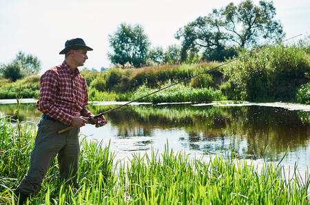 bank activities: Fisher man fishing with spinning rod on a river bank in summer Stock Photo