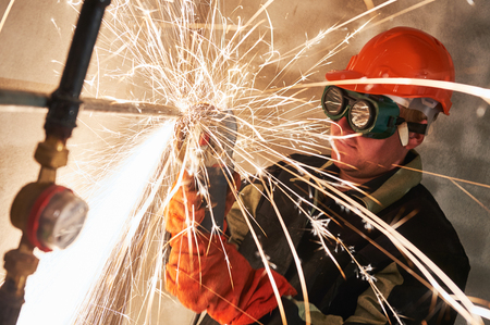 grinder: Construction worker in protective glasses cutting metal pipe at building site with sparks by grinding machine