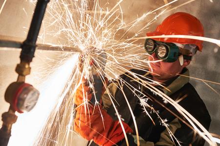 molinillo: trabajador de la construcción en gafas protectoras de corte tubo de metal en obras de construcción con las chispas por la máquina de pulir