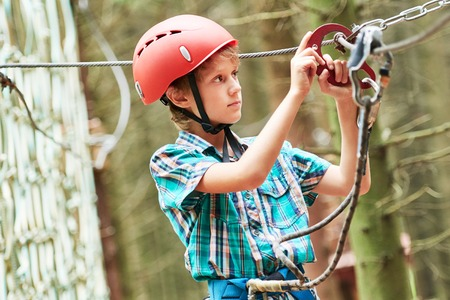 ropeway: Adventure rope way and extreme activity. Scout boy climbing on high wire park in the forest