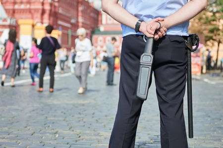 security safety: city safety and security. policeman watching order holding metal detector scanner wand in the urban street