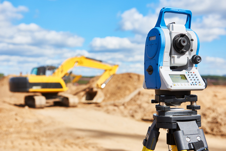 teodolito: taquímetro del equipo del topógrafo o teodolito al aire libre en el sitio de construcción en frente de la excavadora cargadora Foto de archivo