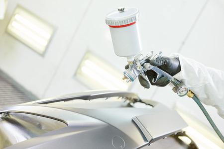 reparador de automóviles pintor mecánico de la mano en la pintura ropa de trabajo parachoques del coche de protección corporal en cámara de pintura en la estación de servicio de garaje.