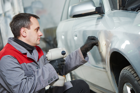 paint samples: auto colour matching. colourist man comparing or selecting color of car at automobile repair and renew service station with paint samples Stock Photo