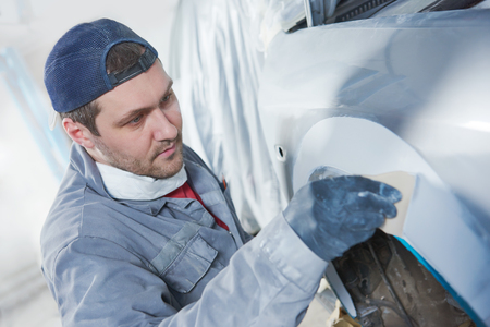 priming paint: Auto body repairs. Repairman mechanic worker plastering automobile car body by plaster in garage workshop Stock Photo