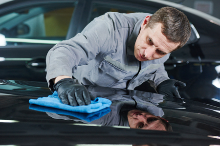 Auto perairing works. Repair man worker polishing automobile car body after painting in garage
