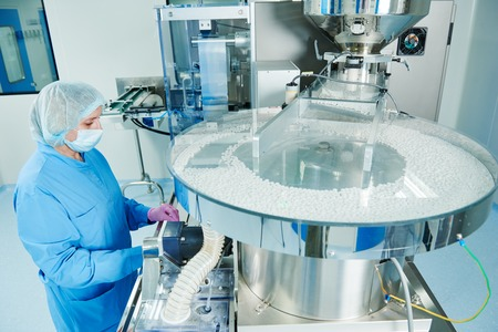 Pharmaceutics. Pharmaceutical industry worker operates tablet blister and cartoning packaging machine at factory Stock Photo - 62489069