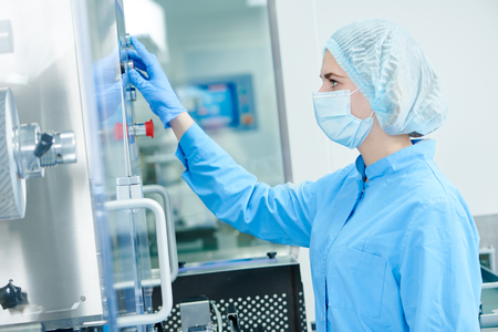 pharmaceutics: Pharmaceutics tablet production. Pharmaceutical industry worker operates blister and cartoning packaging machine at factory Stock Photo