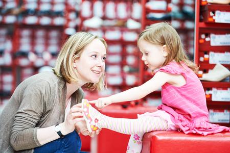 tienda zapatos: las compras de zapatos de la familia. madre de la mujer joven con el calzado hija niña niño elegir Foto de archivo