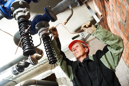 work worker: Plumber work. Construction worker installing water high pressure pump in boiler room Stock Photo