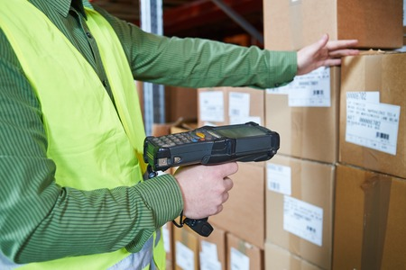 warehouseman worker using wireless barcode scanner. Warehouse Management System