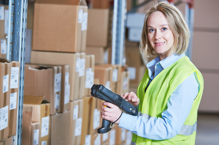 warehouseman: female warehousing worker in storehouse with wireless barcode scanner. Warehouse Management System