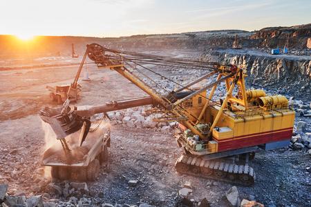 basurero: Industria minera. Pesada excavadora de carga de roca de granito o de mineral de hierro en el enorme camión volcado en la cantera a cielo abierto. La puesta del sol