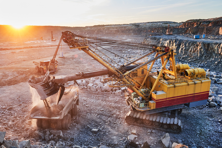 Mining industry. Heavy excavator loading granite rock or iron ore into the huge dump truck at opencast quarry. Sunset Stock Photo