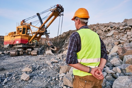 extracting: Construction worker supervising heavy excavator extracting granite rock or iron ore at opencast mining quarry Stock Photo