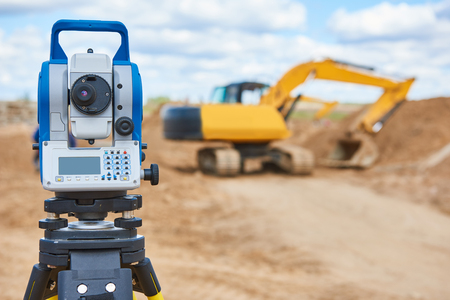 tacheometer: Surveyor equipment tacheometer or theodolite outdoors at construction site in front of loader excavator