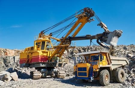 Ciężka koparka ładuje granitową skałę lub rudę żelaza do wielkiej wywrotki w kopalni odkrywkowej