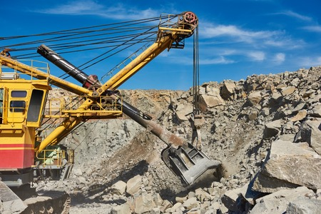 extracting: Mining technology. Heavy excavator extracting granite rock or iron ore at opencast quarry
