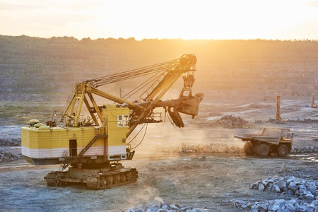 Mining industry. Heavy excavator and big dump truck at sunset during granite rock or iron ore production at opencast quarry. Sunset Stock Photo