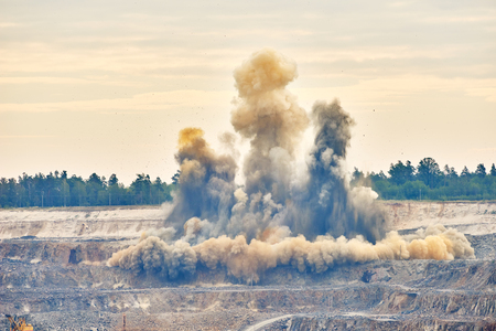 blasted: Mining industry. Big explosion blast on ground for extracting granite rock or metal iron ore at opencast quarry mine