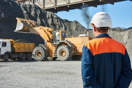 採鉱産業。ダンプカーに花崗岩の岩や鉱石を読み込み重いホイール ローダーを見て建設労働者エンジニア監督