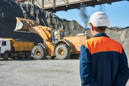 Mining industry. Construction worker engineer supervisor looking at heavy wheel loader loading granite rock or ore into dumper truck Фото со стока