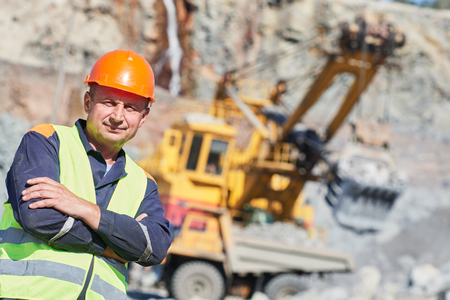 dumper: mining industry. Construction worker in front of working excavator and dumper truck at quarry Stock Photo