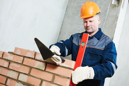 bricklayer: Bricklaying construction worker. Mason bricklayer installing red brick with trowel putty knife outdoors