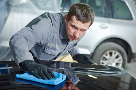 Auto repairing works. Service mechanic man worker polishing automobile car body after painting in garage
