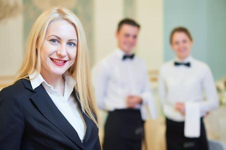 Cateringtjänster. Restaurangchef porträtt framför servitör och servitris personal vid festsal under evenemanget. Stockfoto