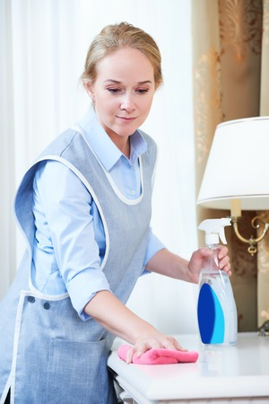 hotel staff: Cleaning service. Female hotel staff worker clean furniture dust
