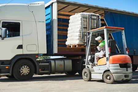 Loading werken. Lader van de vorkheftruck bewegende pallet met lading in lading vrachtwagen