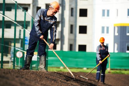 paysagiste: Deux travailleurs de la construction municipales rendant l'amélioration urbaine, l'aménagement paysager et d'embellissement Banque d'images