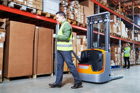 Warehousing. workers using forklift loader stacker and wireless barcode scanner. Warehouse Management System photo