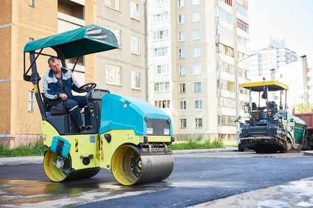 compacting: Road construction. Worker on steam vibration roller compacting asphalt way