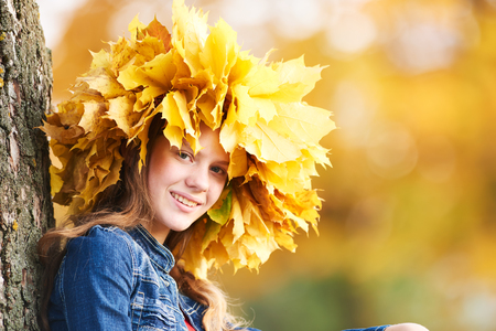 Portrait of young girl in autumn orange leaves chaplet or circlet. Outdoors.